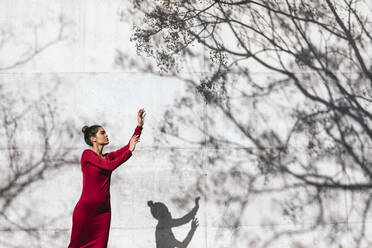 Woman in red dress with dancer pose and tree shadows on  wall - TCEF00622