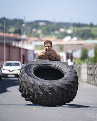 Athlete exercising with tractor tire on a road - SNF00185