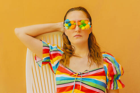 Portrait of woman wearing glasses with colourful pom poms covering her eyes - ERRF03677