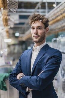 Portrait of a confident young businessman in a factory - DIGF10716