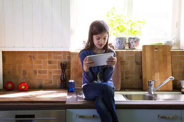Girl sitting on sink in the kitchen looking at digital tablet - LVF08876