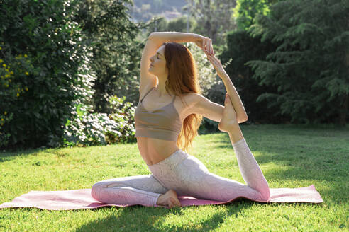 Young woman doing yoga on a mat in grass - AFVF06257