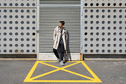 Mid adult man waiting in yellow marked area in front of concrete wall - MAUF03403