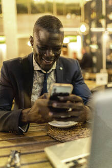 Smiling young businessman using smartphone in a coffee shop - EGAF00088