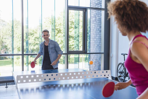 Young business people plaing table tennis in loft office - DIGF10850