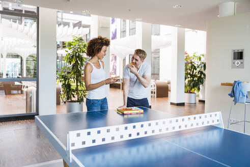 Young business people sharing pizza for lunch in a modern office with ping pong table - DIGF10865