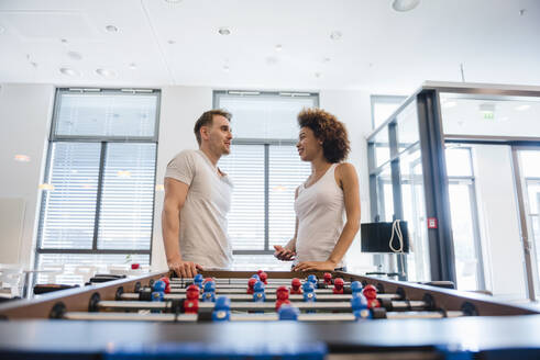 Young man amnd woman talking in office with a football table - DIGF10871