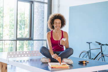 Young woman sitting on ping pong table, eating pizza, using laptop - DIGF10877
