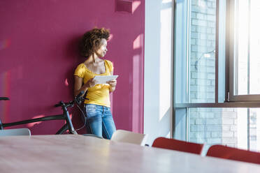 Young woman standing in front of read wall, looking out of window, holding digital tablet - DIGF10880