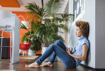 Young businesswoman sitting on floor, relaxing with a cup of coffee - DIGF10886