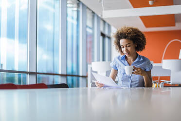 Young woman sitting in modern office, drinking coffee, reading papers - DIGF10895
