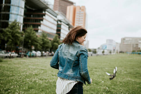 Germany, Berlin, Rear view of young woman wearing denim jacket - VBF00038