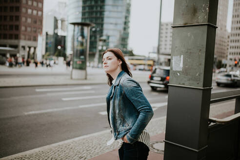 Germany, Berlin, Portrait of young woman waiting on sidewalk - VBF00041