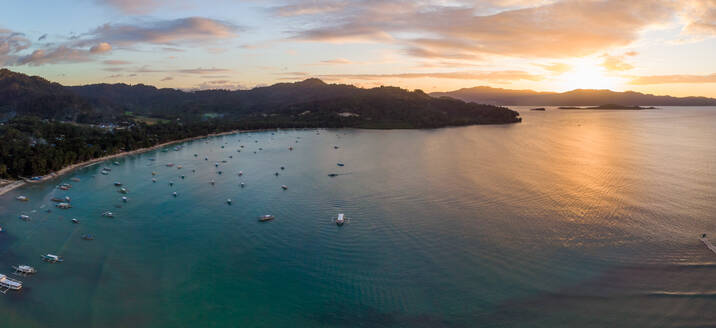 Panoramic aerial view of sunset over the tourist spot Port Barton, showing the beach and outrigger boats in the bay. Port Barton, Palawan, Philippines - AAEF08424