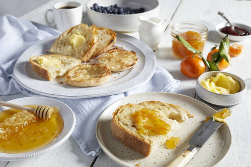 Plates of toast with butter and marmalade, dishes of honey, butter and jams. - CUF55007