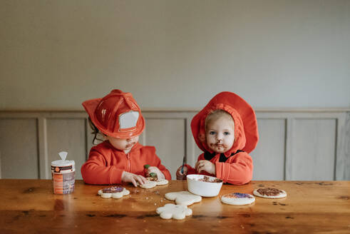 Two children dressed as firefighters at a table decorating  cookies with chocolates and sprinkles. - ISF24083