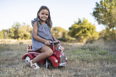 Portrait of smiling little girl with pedal car in nature - SNF00189