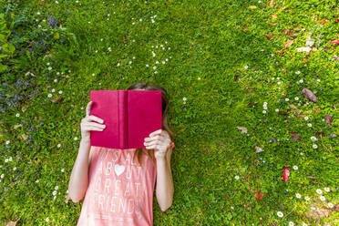 Girl lying on meadow reading a book, top view - SARF04566