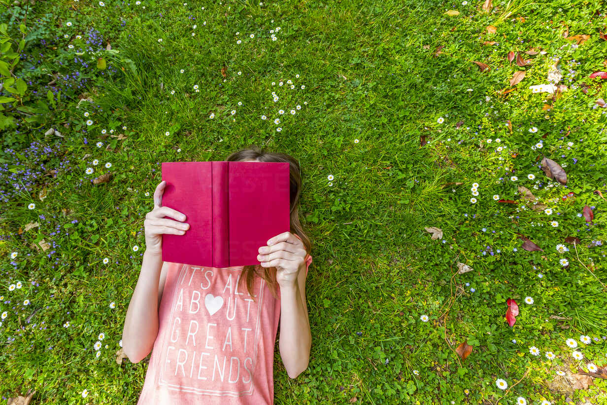 Girl lying on meadow reading a book, top view - SARF04566 - Sandra Roesch/Westend61