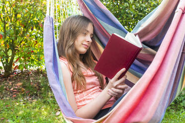 Portrait of girl reading book in hammock - SARF04578