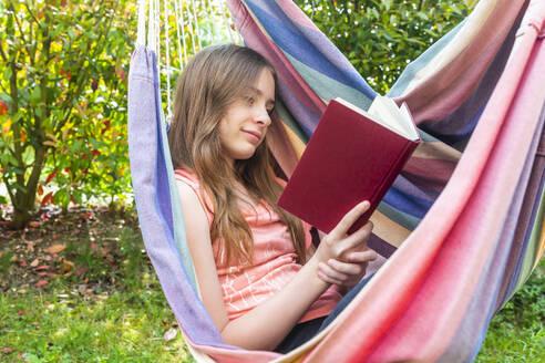 Portrait of girl reading book in hammock - SARF04578
