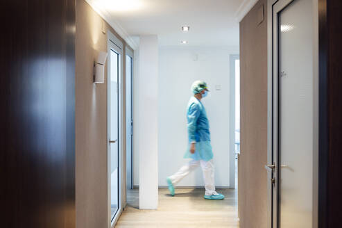 Mature male dentist walking in illuminated hallway at medical clinic - JCMF00727