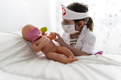 Girl in doctor's costume caring of her doll with a mask - EGAF00097