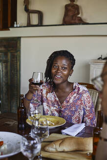 Smiling young woman holding wineglass while sitting at dining table during lunch - VEGF02224