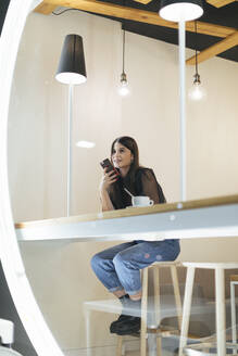 Full length of beautiful woman sitting with smart phone and coffee at cafe - OCAF00476