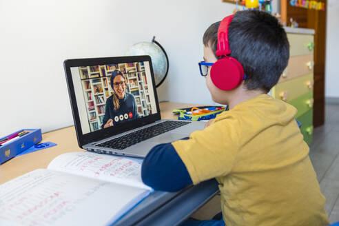 Boy listening to teacher through headphones during video call at home - MGIF00953
