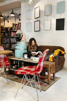 Woman reading a book in coffee shop - MGOF04246