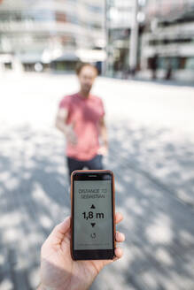Close-up of man holding smartphone showing distance on display - JOSEF00550