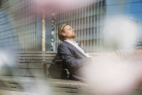 Businessman relaxing on a bench in the city - JOSEF00595