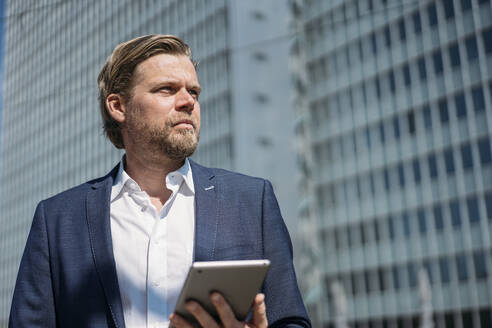 Portrait of businessman holding tablet in the city - JOSEF00598