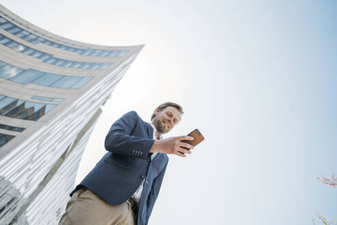Smiling businessman using smartphone in the city - JOSEF00607