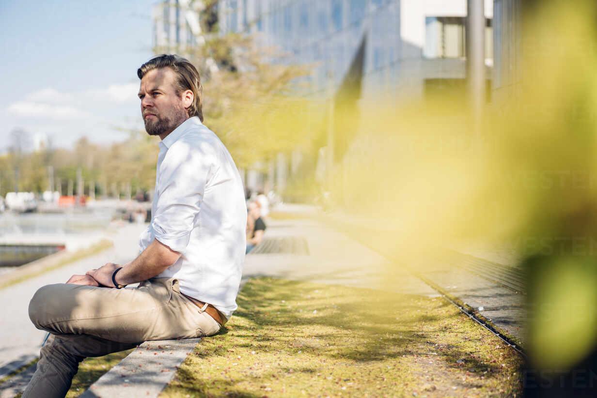 Businessman having a break in the city sitting on a wall - JOSEF00637 - Joseffson/Westend61