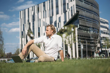 Businessman with laptop sitting in grass in the city - JOSEF00652