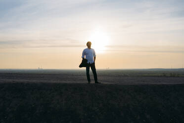 Male entrepreneur standing on hill against sky during sunset - MOEF02888