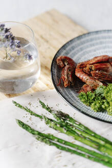 Grilled prawns, parsley and asparagus on wooden cutting board - JMHMF00049