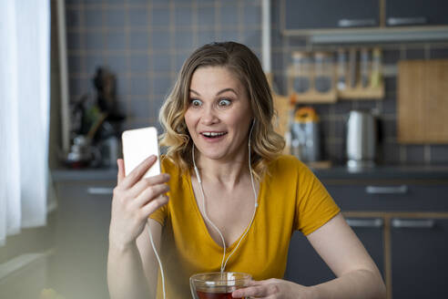 Surprised woman having a video chat with smartphone in kitchen at home - VPIF02458