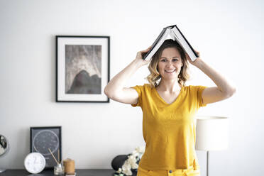 Portrait of smiling woman at home holding book above her head - VPIF02482