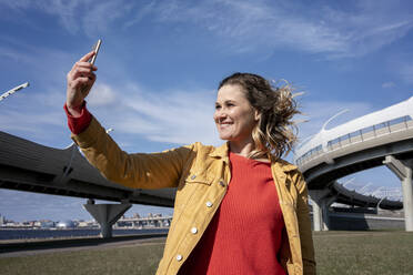 Happy woman with windswept hair taking a selfie at a road bridge - VPIF02497