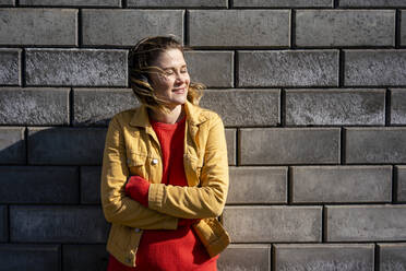 Smiling woman standing at a brick wall listening to music with headphones - VPIF02500