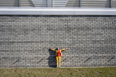 Woman standing at a brick wall listening to music with headphones - VPIF02503