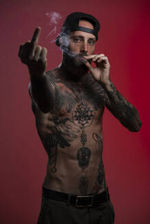Portrait of tattooed man against red background giving the finger while smoking a joint - AMUF00109