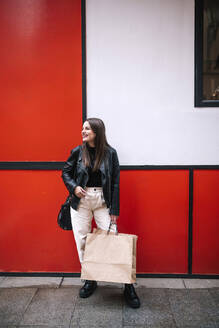 Happy young woman with shopping bags in the city - GRCF00231