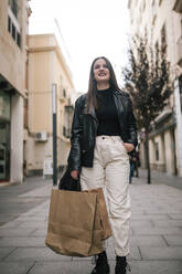 Portrait of happy young woman with shopping bags in the city - GRCF00234