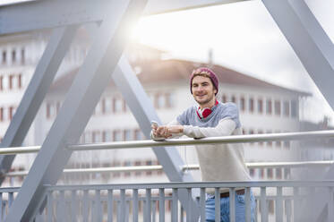 Stylish young man holding smartphone on a bridge - DIGF10907