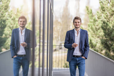 Young businessman holding smartphone at an office building - DIGF10925