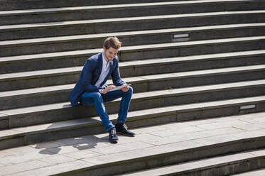 Young businessman sitting on stairs using tablet - DIGF10931